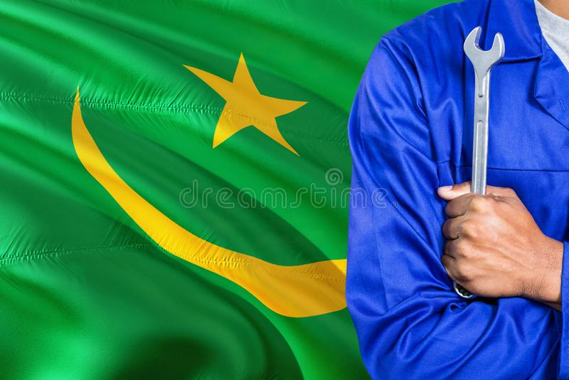 Mauritanian Mechanic in blue uniform is holding wrench against waving Mauritania flag background. Crossed arms technician stock photos