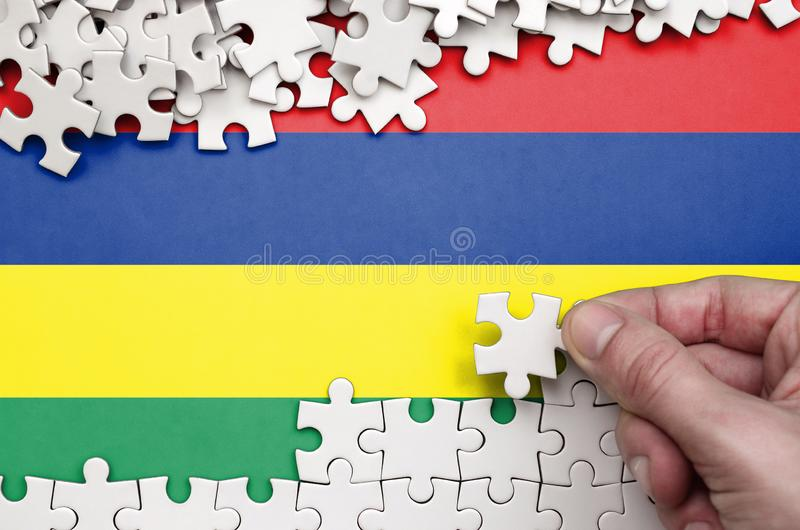 Mauritius flag is depicted on a table on which the human hand folds a puzzle of white color stock image