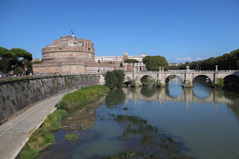 Mausoleum Castel Sant Angelo in Rome. The Castle connected to the Vatican. The bridge in front of the Castle is reflected on the water surface. Blue sky on a royalty free stock photos