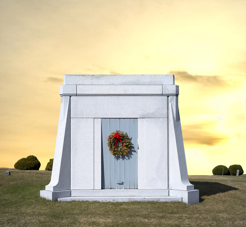 Mausoleum with wreath on door. A stone mausoleum with an old wreath on door with yellow sky stock photo