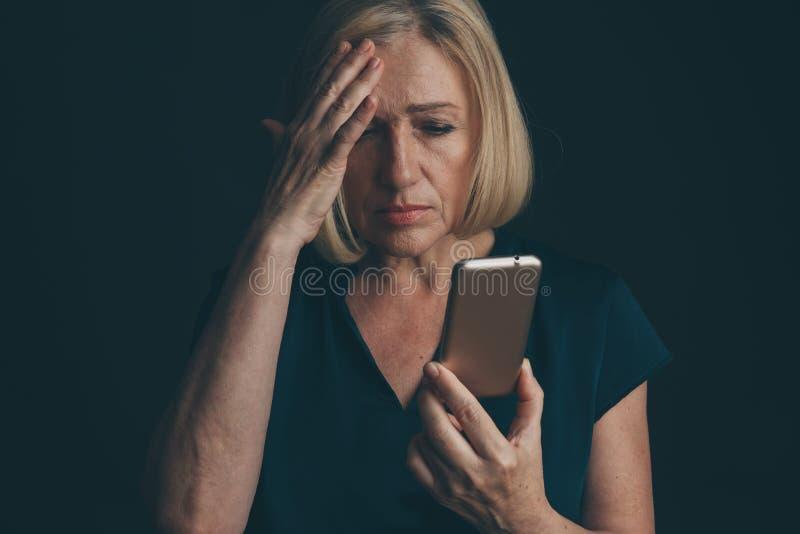 Mauvais concept de nouvelles de téléphone Mobile se tenant femelle avec le visage triste image libre de droits