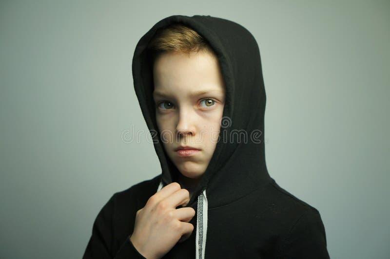 Mauvais garçon adolescent avec la fronde et la coupe de cheveux élégante, tir de studio photographie stock libre de droits