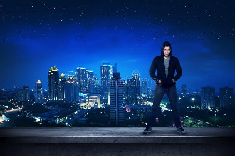 Mauvais garçon se tenant sur le dessus de toit de bâtiment photos libres de droits