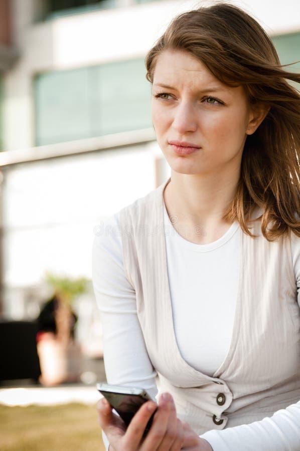 Mauvais message - femme malheureuse avec le téléphone image stock