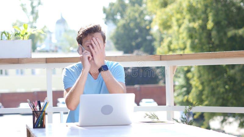 Mauvaise nouvelle sur l'appel téléphonique, jeune homme malheureux et bouleversé photo stock
