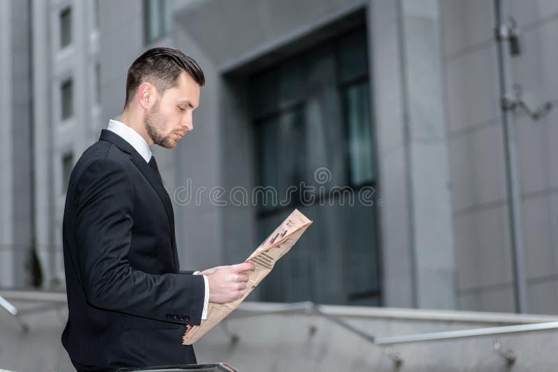 Mauvaises nouvelles Vue de côté d'un homme d'affaires lisant un journal qui fi images libres de droits