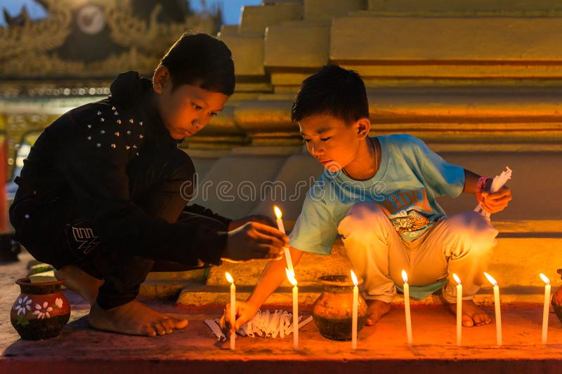 Unidentified burmese boys fire candles in buddhist temple during Thadingyut or Lighting Festival in Mawlamyine, Burma. Mawlamyine, Myanmar - October 16, 2016 stock images