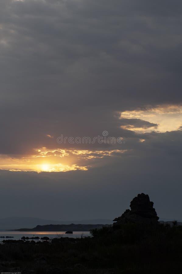 Maxima för en morgonsoluppgång till och med tunga moln som avslöjer en kontur av en tufa på den mono sjön royaltyfri fotografi