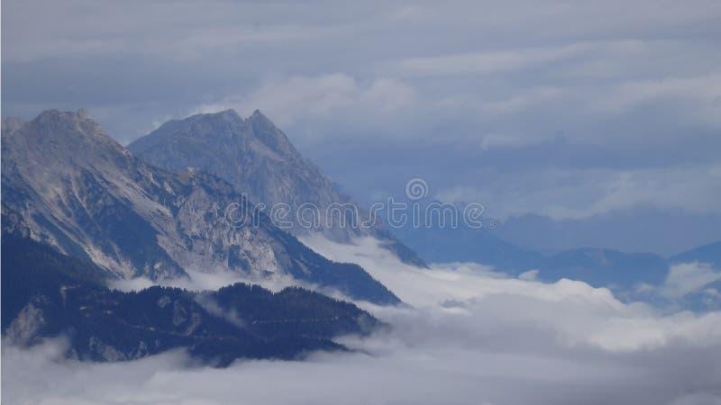Maxima för högt berg som stiger från dimman i dalen royaltyfri foto
