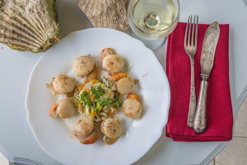 Maximus Pecten που μαγειρεύεται στο άσπρο κρασί στο άσπρο πιάτο, εκλεκτής ποιότητας μαχαιροπήρουνα στην κόκκινη πετσέτα, ποτήρι τ στοκ φωτογραφία με δικαίωμα ελεύθερης χρήσης