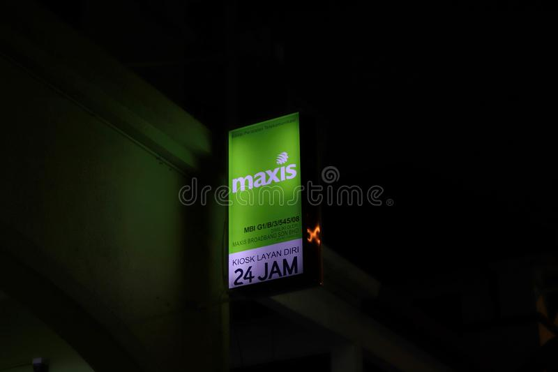 Maxis Self-service Electrical Signboard At Night. Bottom-up view of the Maxis Malaysia`s electrical signboard at night. Writings on the signboard is written in stock images