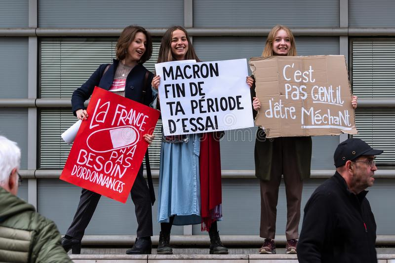 May 2018 - Anti Macron protest in Paris. Three young girls hold placards against Emmanuel Macron`s reforms royalty free stock images