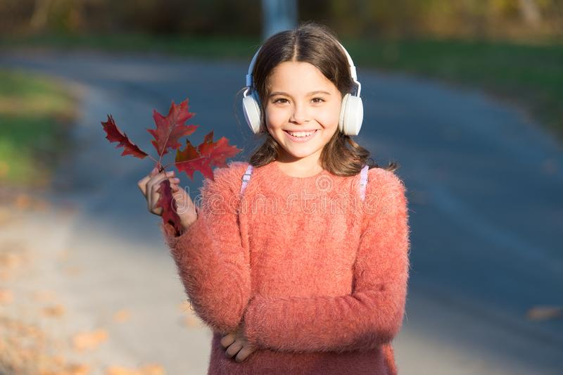 May this autumn be as melodious as happy song. Happy small girl listen to music on autumn landscape. Little child enjoy. Listening to happy melody. Happy hour royalty free stock image