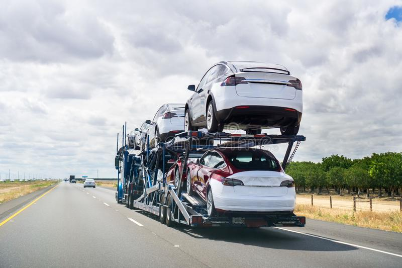 May 25, 2018 Bakersfield / CA / USA - Car transporter carries Tesla Model 3 new vehicles along the highway, back view of the. Trailer stock photos