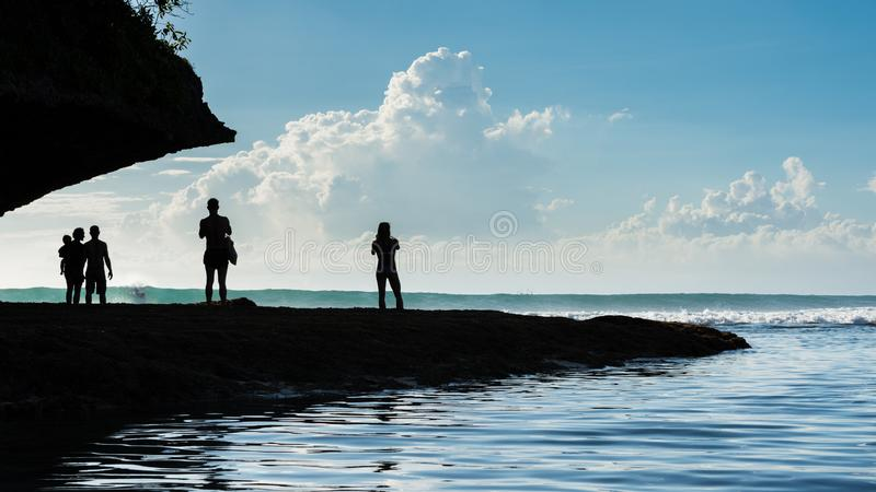 Silhouetted people watch as surfers get some nice waves in Bali royalty free stock photography
