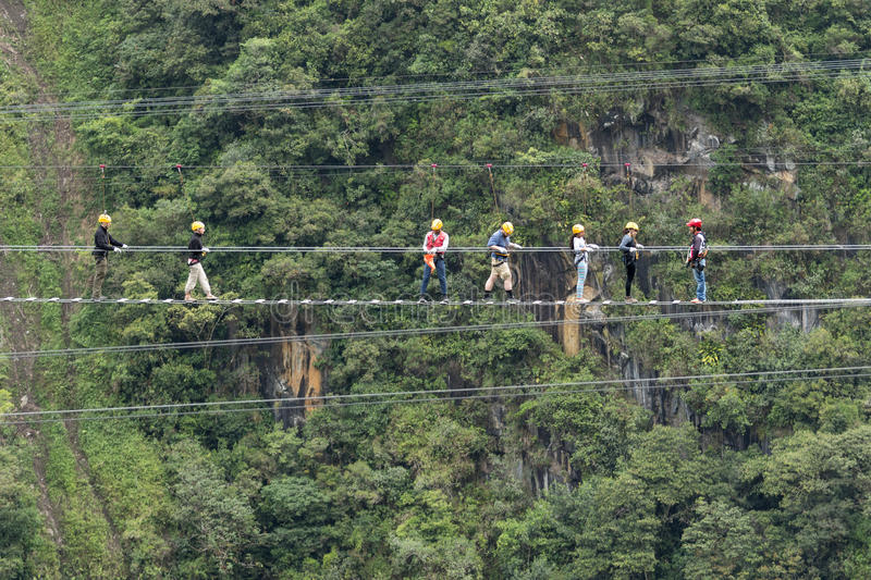Tourists walking a suspended cable bridge in Ecuador stock photography