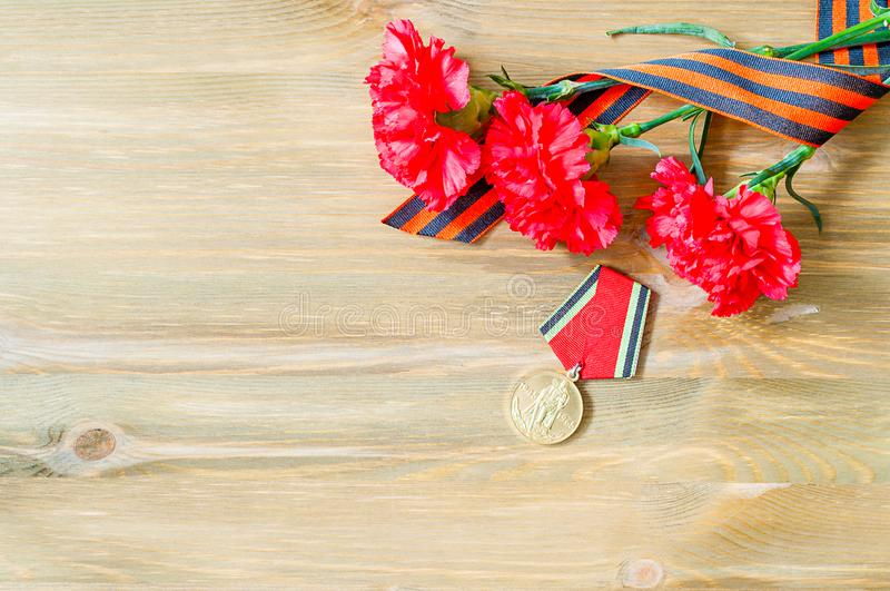 9 May card - jubilee medal of Great patriotic war with red carnations and St George ribbon royalty free stock photography