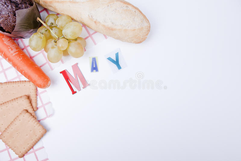 May. Creative May composition, napkins, grapes, carrot, chocolate muffin and biscuits, separate calendar page with copy space royalty free stock image