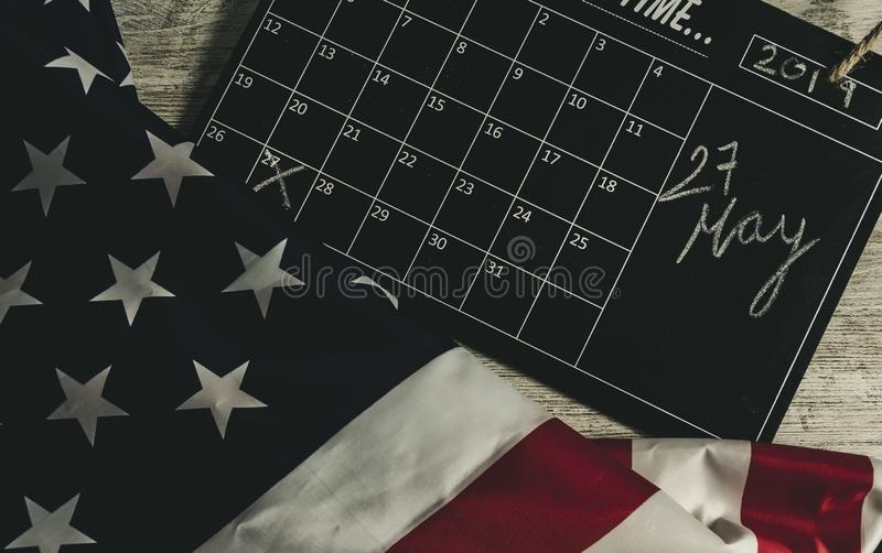 27 May date in calendar under american states flag, and all on wooden table, vintage style stock photography