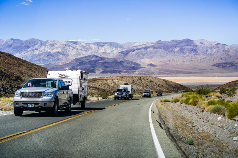May 28, 2018 Death Valley / CA / USA - Pick up trucks with RV travel trailers driving though Death Valley National Park; Panamint stock images