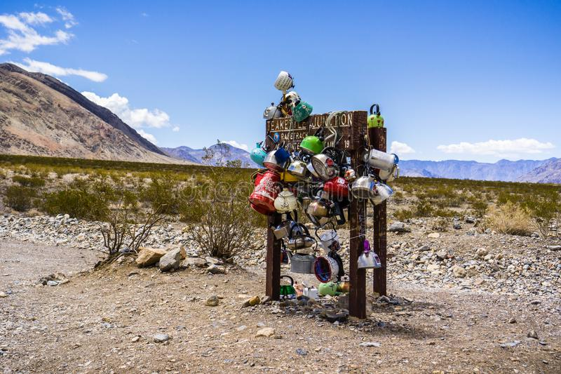 May 27, 2018 Death Valley / CA / USA - Teakettle Junction sign covered in tea kettles left by visitors stock images
