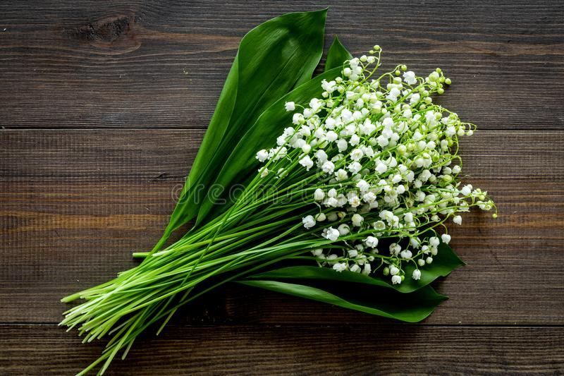 May flowers. Bouqet of lily of the valley flowers on dark wooden background top view.  royalty free stock images