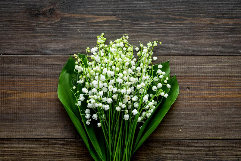 May flowers. Bouqet of lily of the valley flowers on dark wooden background top view copy space. May flowers. Bouqet of lily of the valley flowers on dark wooden stock photos