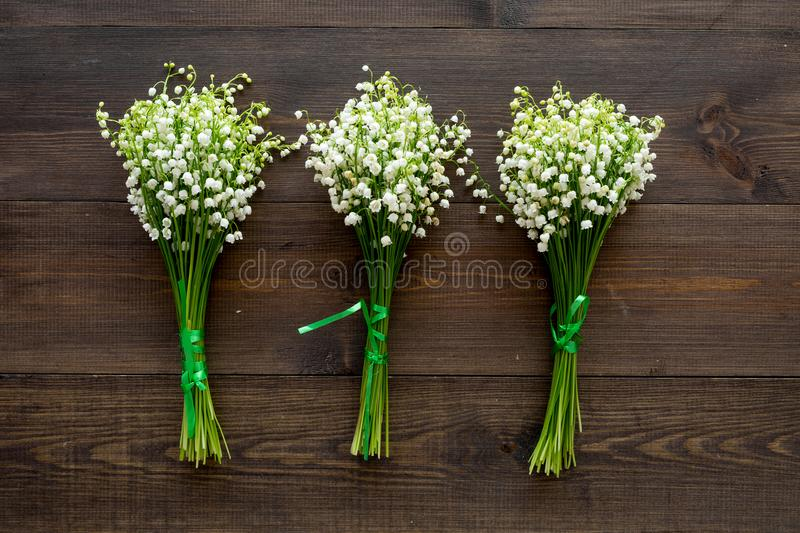 May flowers. Bouqet of lily of the valley flowers on dark wooden background top view.  stock image