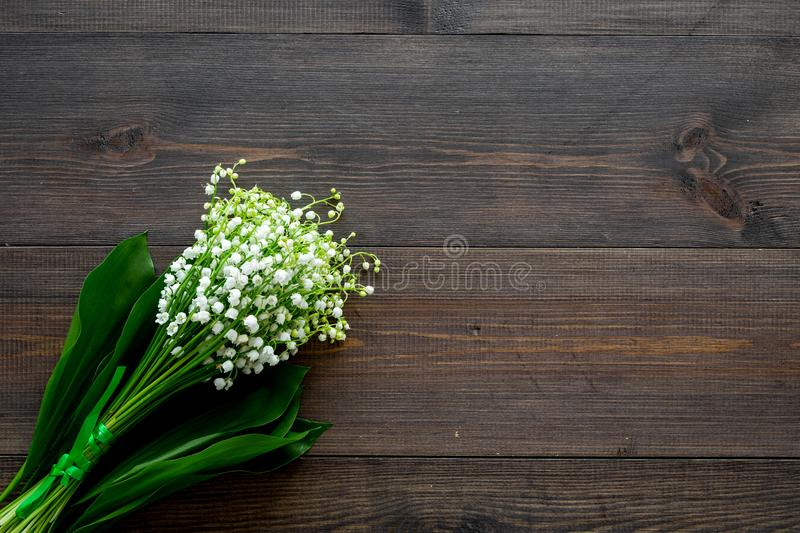 May flowers. Bouqet of lily of the valley flowers on dark wooden background top view copy space. May flowers. Bouqet of lily of the valley flowers on dark wooden stock image