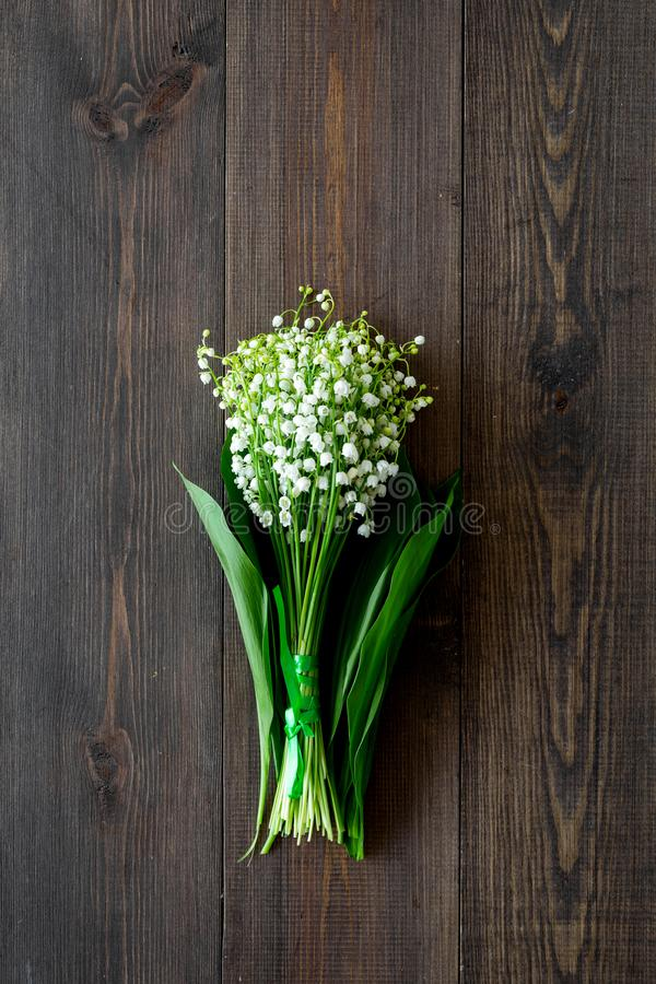 May flowers. Bouqet of lily of the valley flowers on dark wooden background top view copy space. May flowers. Bouqet of lily of the valley flowers on dark wooden royalty free stock images