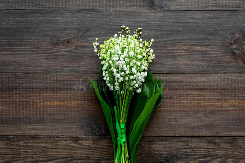 May flowers. Bouqet of lily of the valley flowers on dark wooden background top view copy space. May flowers. Bouqet of lily of the valley flowers on dark wooden stock photo