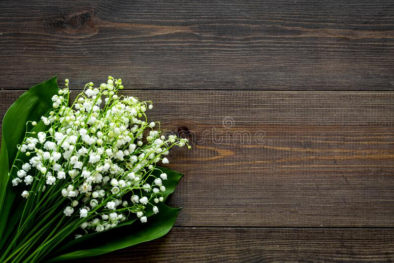 May flowers. Bouqet of lily of the valley flowers on dark wooden background top view copy space. May flowers. Bouqet of lily of the valley flowers on dark wooden stock images