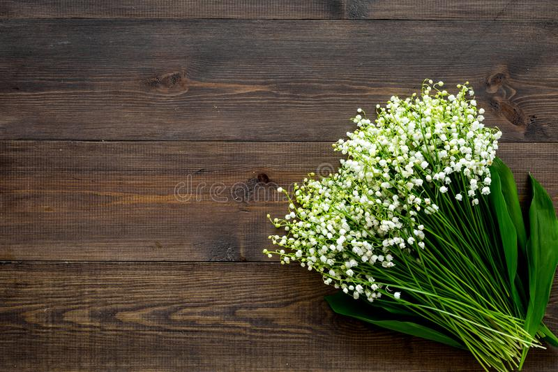 May flowers. Bouqet of lily of the valley flowers on dark wooden background top view copy space. May flowers. Bouqet of lily of the valley flowers on dark wooden royalty free stock photography