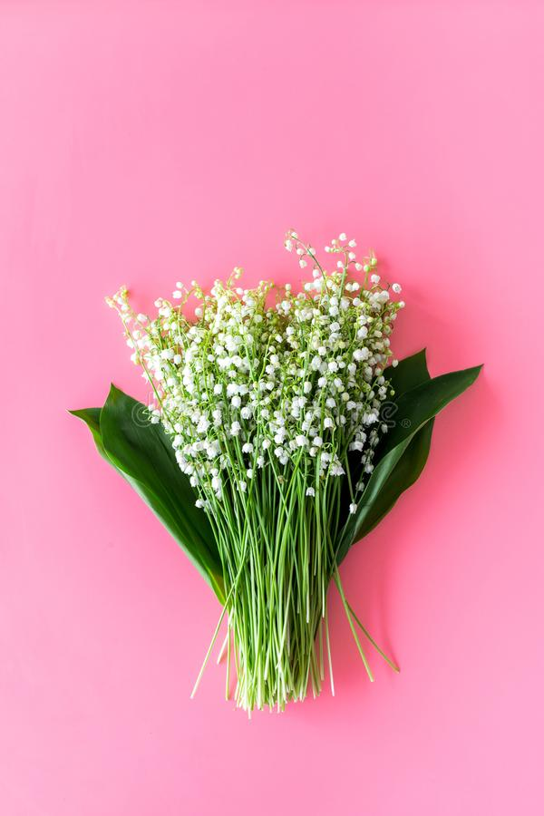 May flowers. Bouqet of lily of the valley flowers on pastel pink background top view copy space. May flowers. Bouqet of lily of the valley flowers on pastel pink stock photos