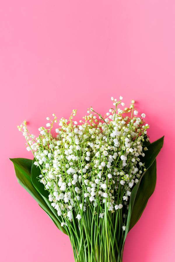 May flowers. Bouqet of lily of the valley flowers on pastel pink background top view copy space. May flowers. Bouqet of lily of the valley flowers on pastel pink royalty free stock photography