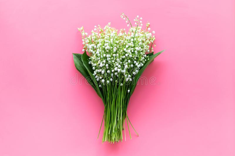 May flowers. Bouqet of lily of the valley flowers on pastel pink background top view copy space. May flowers. Bouqet of lily of the valley flowers on pastel pink stock photography