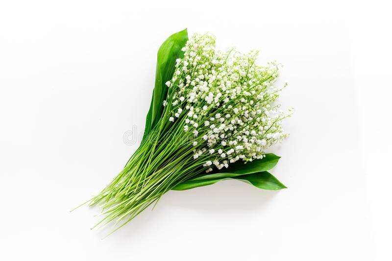 May flowers. Bouqet of lily of the valley flowers on white background top view copy space. May flowers. Bouqet of lily of the valley flowers on white background royalty free stock photo