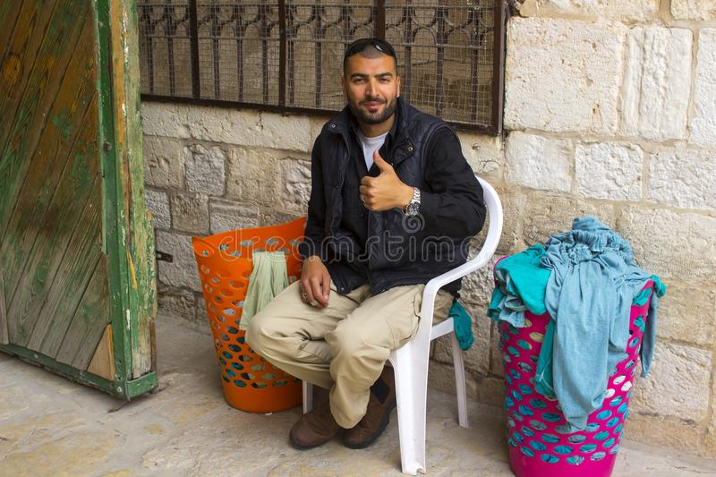 A bearded Muslim male seated at the entrance to the Temple Mount royalty free stock photography