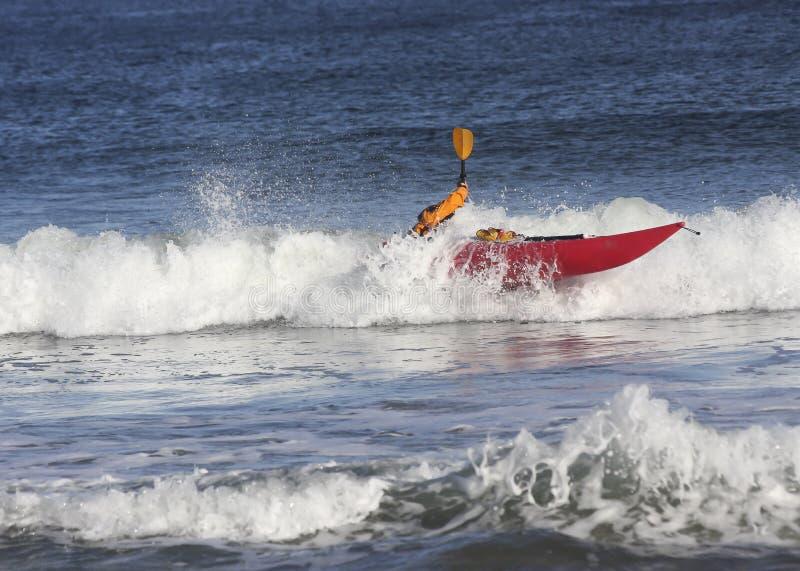 Man with kayak on rough sea