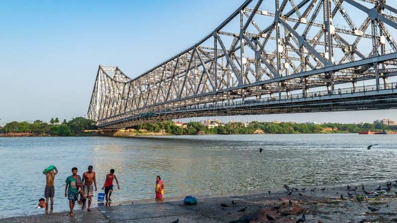 Howrah Bridge or Hooghly bridge. May 27,2018. Kolkata,India. People doing Morning activities on the Bank of Hooghly River overlooking The Howrah Bridge stock photos