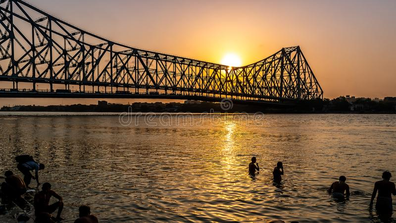 Howrah bridge at the time of Sunrise. May 27,2018. Kolkata, India. Silhouette of Howrah Bridge at the time of Sunrise. People bathing and making rituals in the stock images