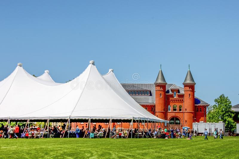May 31 2013 Middletown USA Wesleyan University graduation - tent for celebration with people milling around and sitting under it. On a beautiful sunny day royalty free stock photo