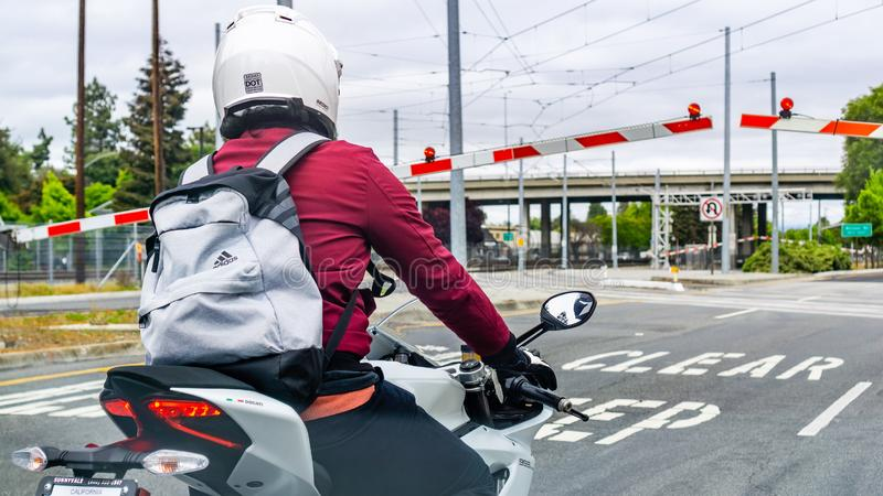 May 9, 2019 Mountain View / CA / USA - Motorcyclist waiting at a barrier in south San Francisco bay area stock photo