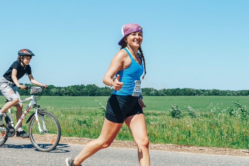 May 26-27, 2018 Naliboki,Belarus All-Belarusian amateur marathon Naliboki A woman runs alongside a cyclist on the road royalty free stock image
