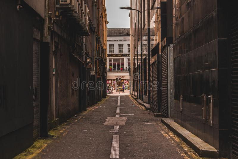 Deserted alleyway next to the busy street of St. Patrick in the heart of the city of Cork in Ireland. May 3rd, 2018, Cork, Ireland - deserted alleyway next to stock photo