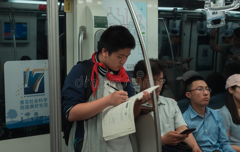 28 May, 2018, Shanghai city, China. Chinese schoolboy does his homework in subway carriage on the way home royalty free stock image