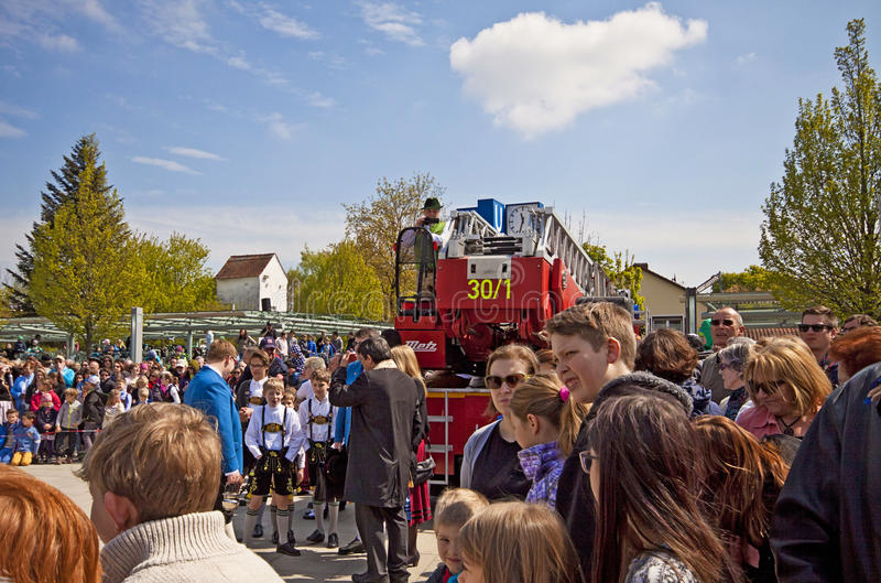 May 1st, Bavarian festival. Garching, Germany - People with the traditional Bavarian costumes and a fire brigade truck wait the new may pole, to be erected in stock photos