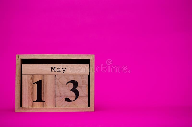 May 13th. Day 13 of may month set on wooden calendar isolated on pink background. Spring time. Empty space for text, mockup royalty free stock photo