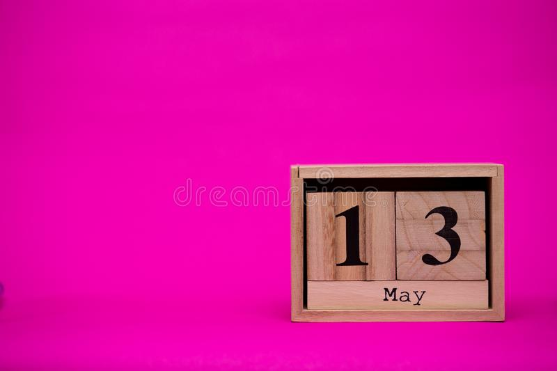 May 13th. Day 13 of may month set on wooden calendar isolated on pink background. Spring time. Empty space for text, mockup royalty free stock image