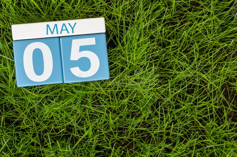 May 5th. Day 5 of month, wooden color calendar on football green grass background. Spring time, empty space for text stock photography